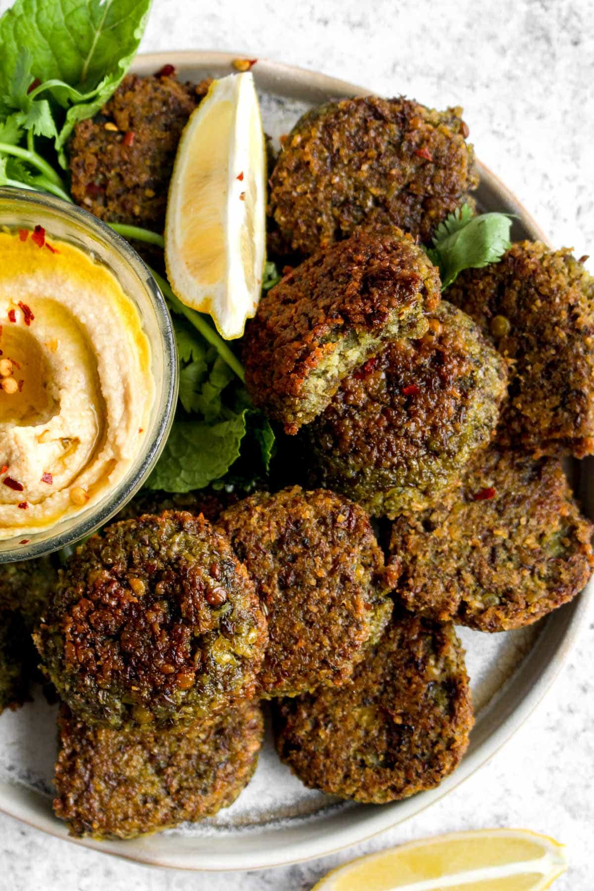 A plate of baked lentil falafel with hummus, cilantro, and mint.