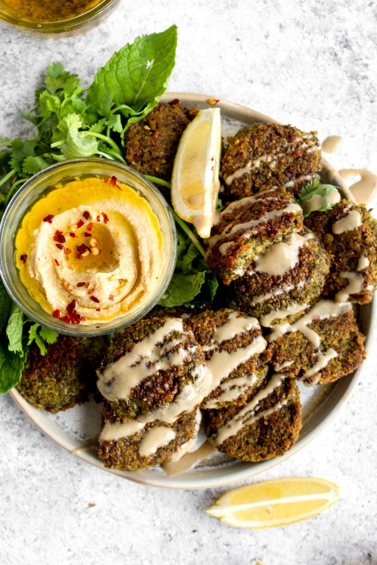 A plate of baked lentil falafel with lemon and tahini sauce.