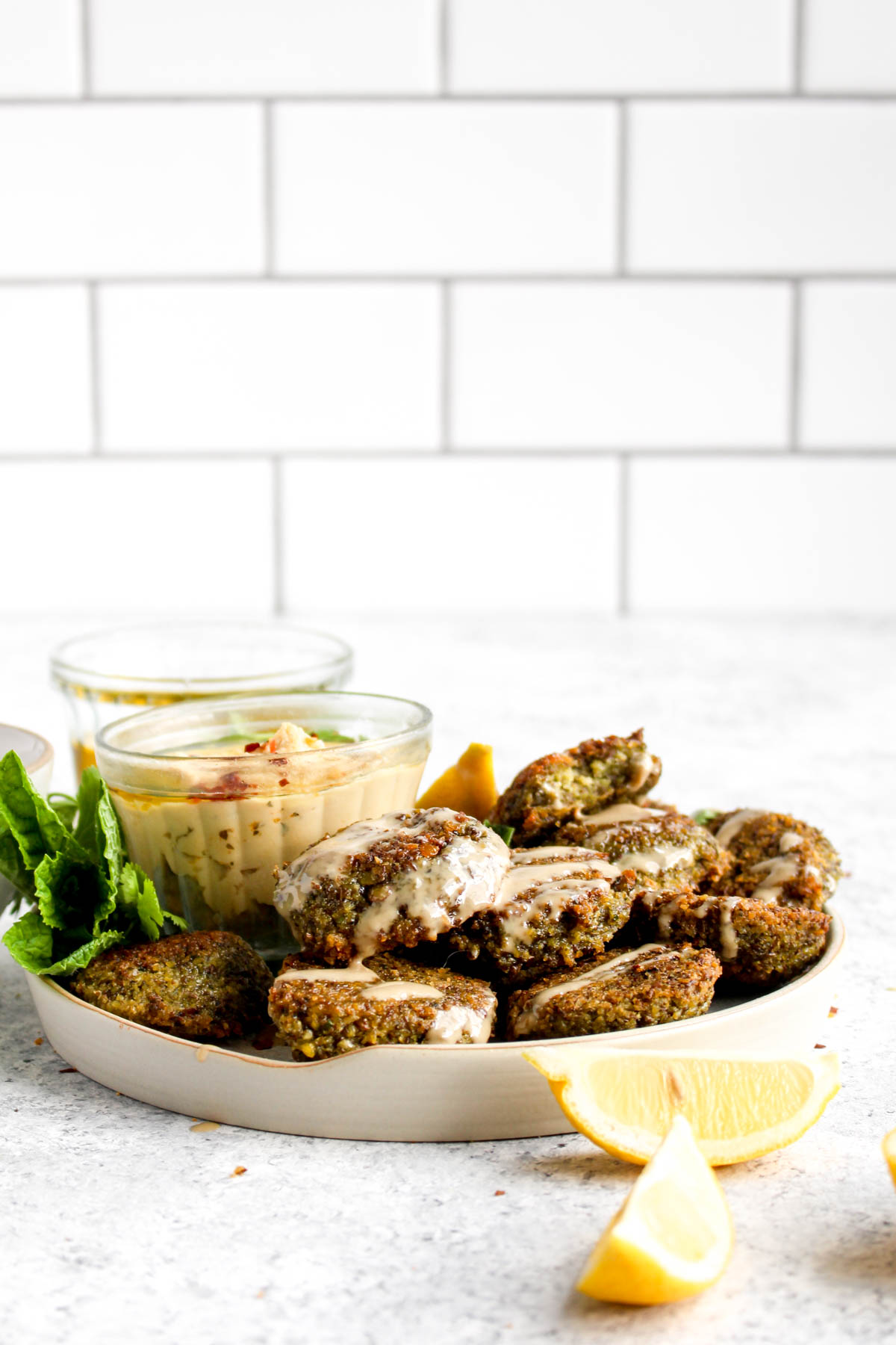 A plate of baked lentil falafel with a tahini drizzle and herbs.