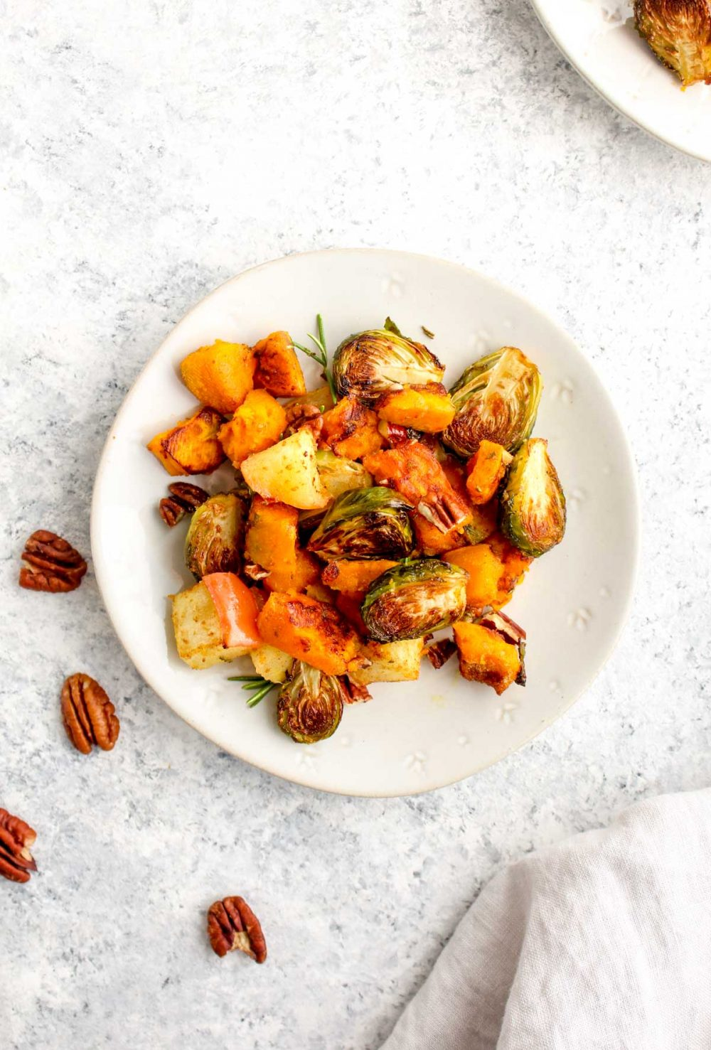 Butternut Squash, Apple, and Brussel Sprout Bake on a plate with rosemary and pecans.