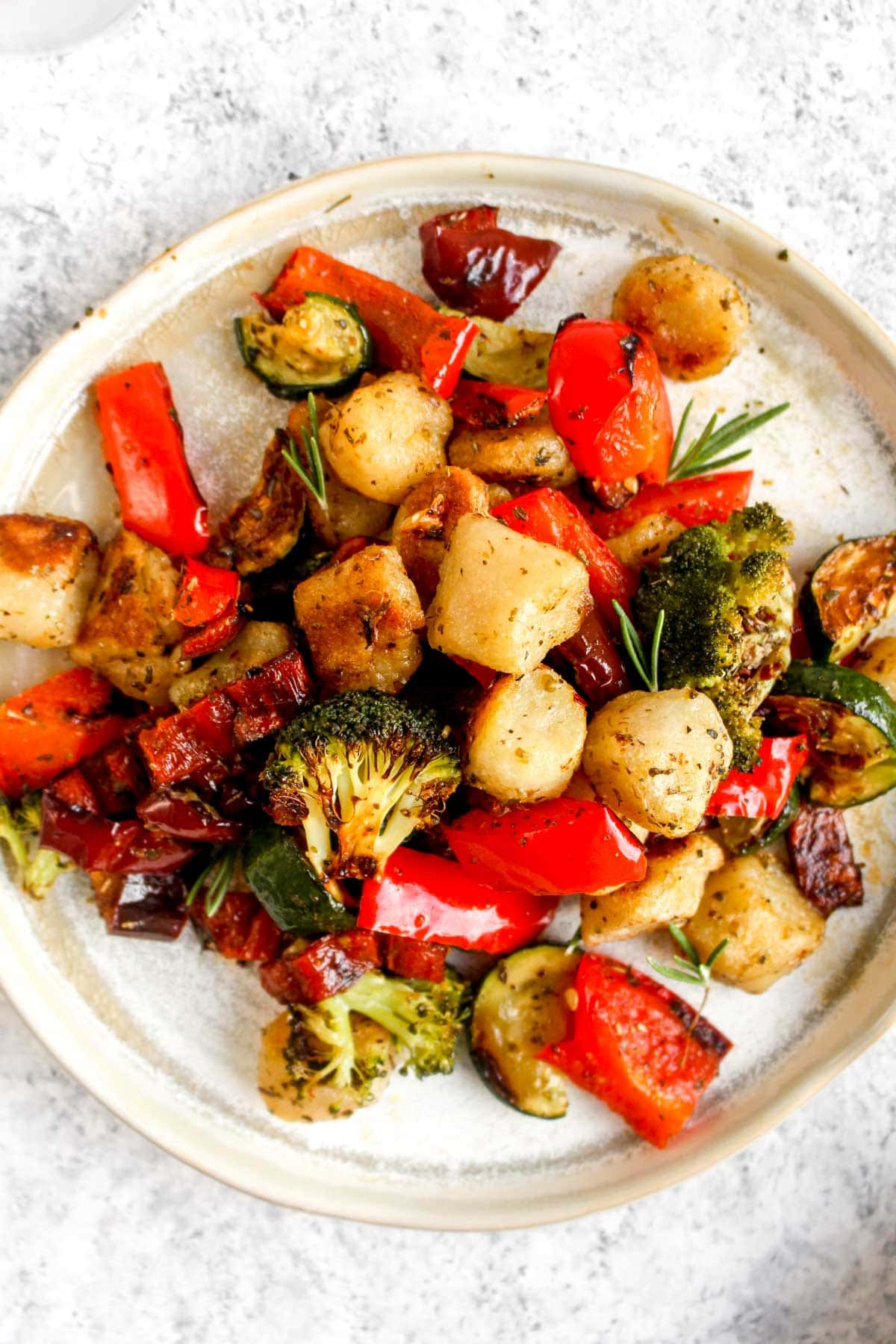 Cauliflower gnocchi sheet pan dinner on a plate with veggies and red pepper flakes.