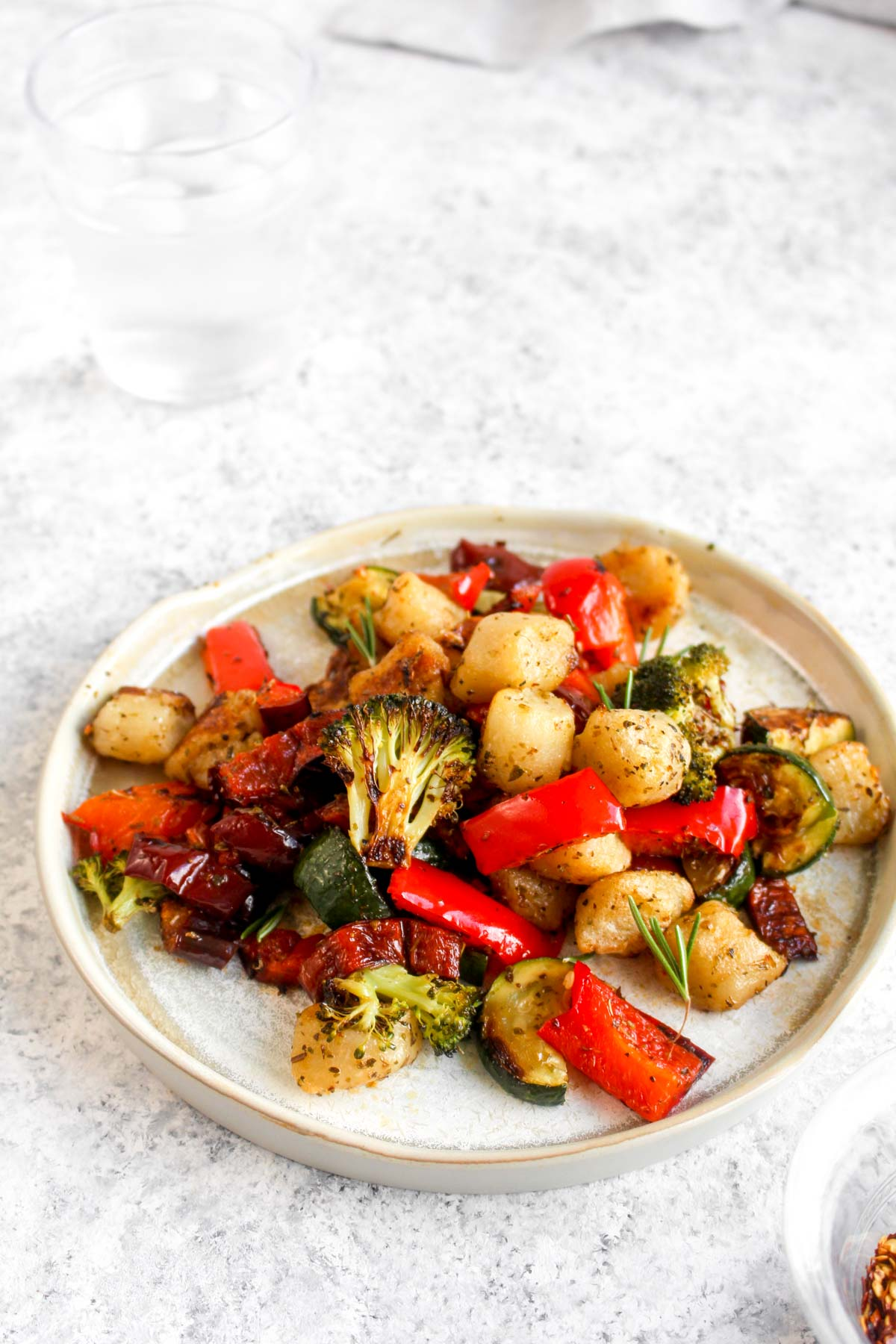 Cauliflower Gnocchi Sheet Pan Meal plated with vegetables and rosemary.