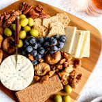 A Vegetarian charcuterie board with grapes, nuts, olives and cheese.