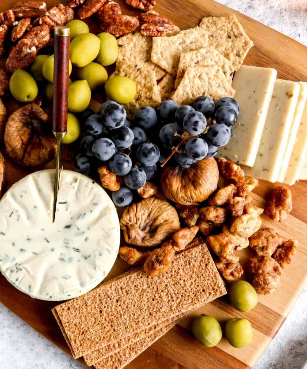 A vegetarian charcuterie board with crackers, dried figs, olives, glazed nuts and dairy free cheeses.