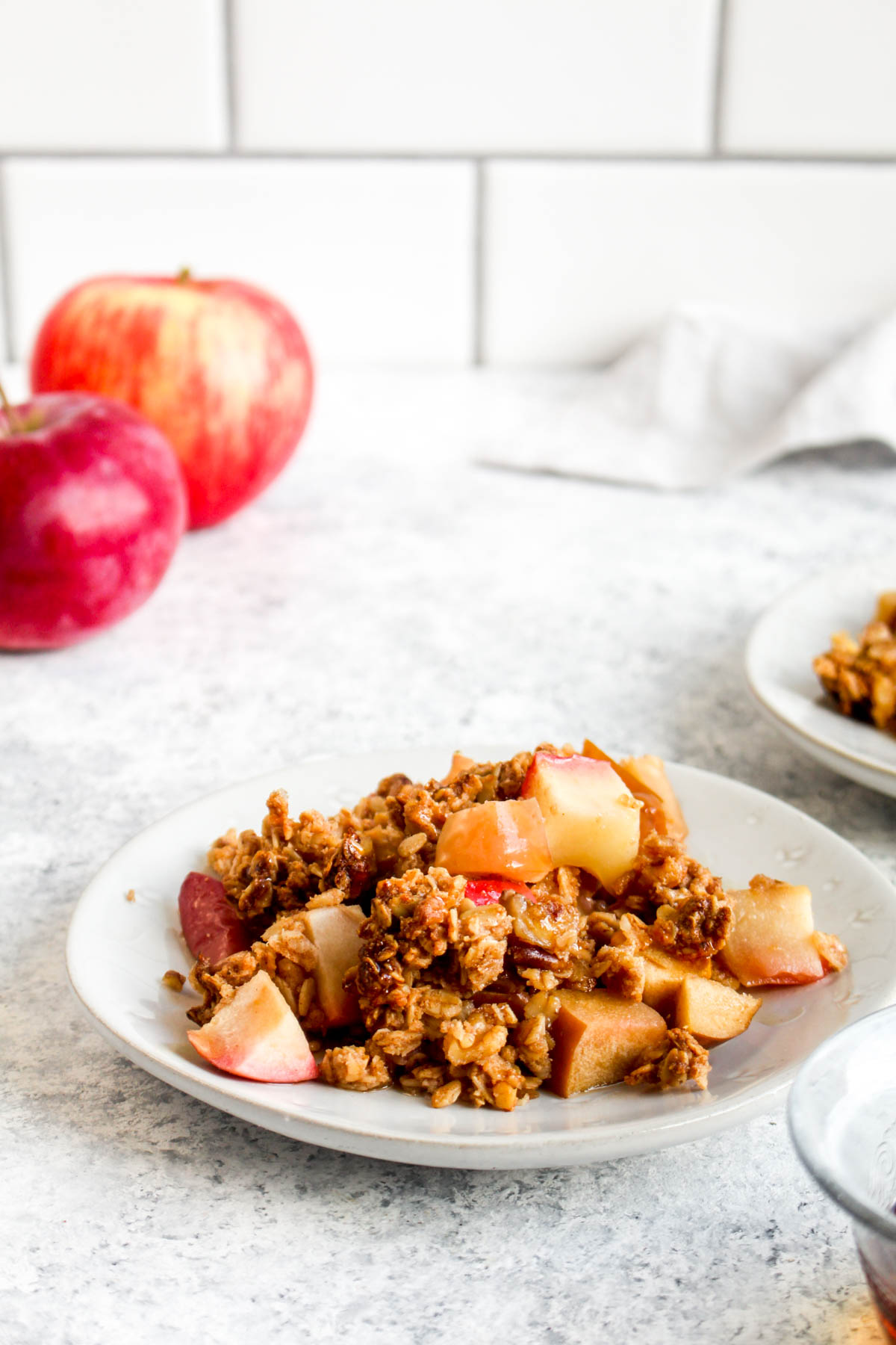 Brunch Apple Crisp on a white plate with apples.