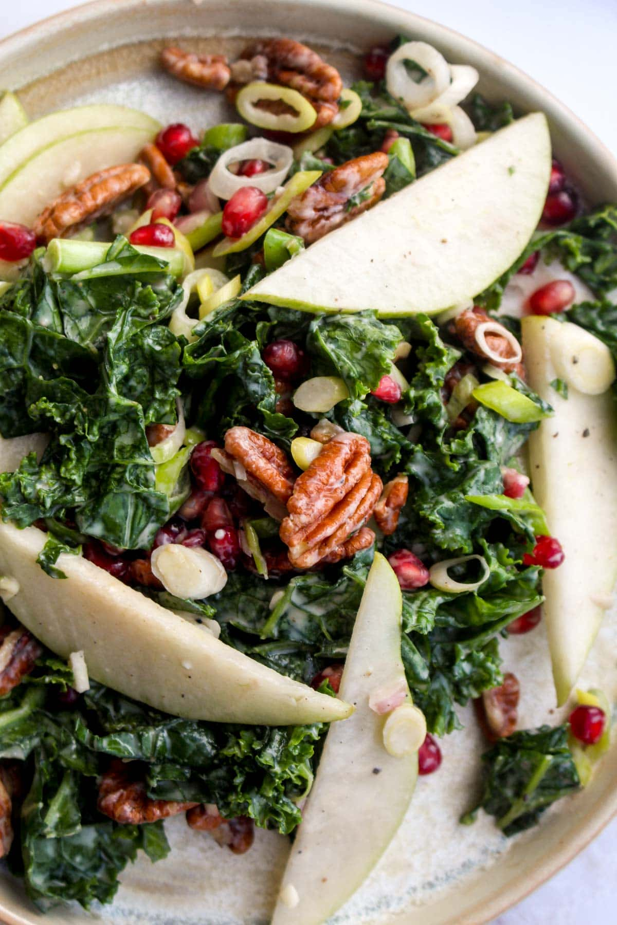 A close up of winter kale salad with pears and pecans.