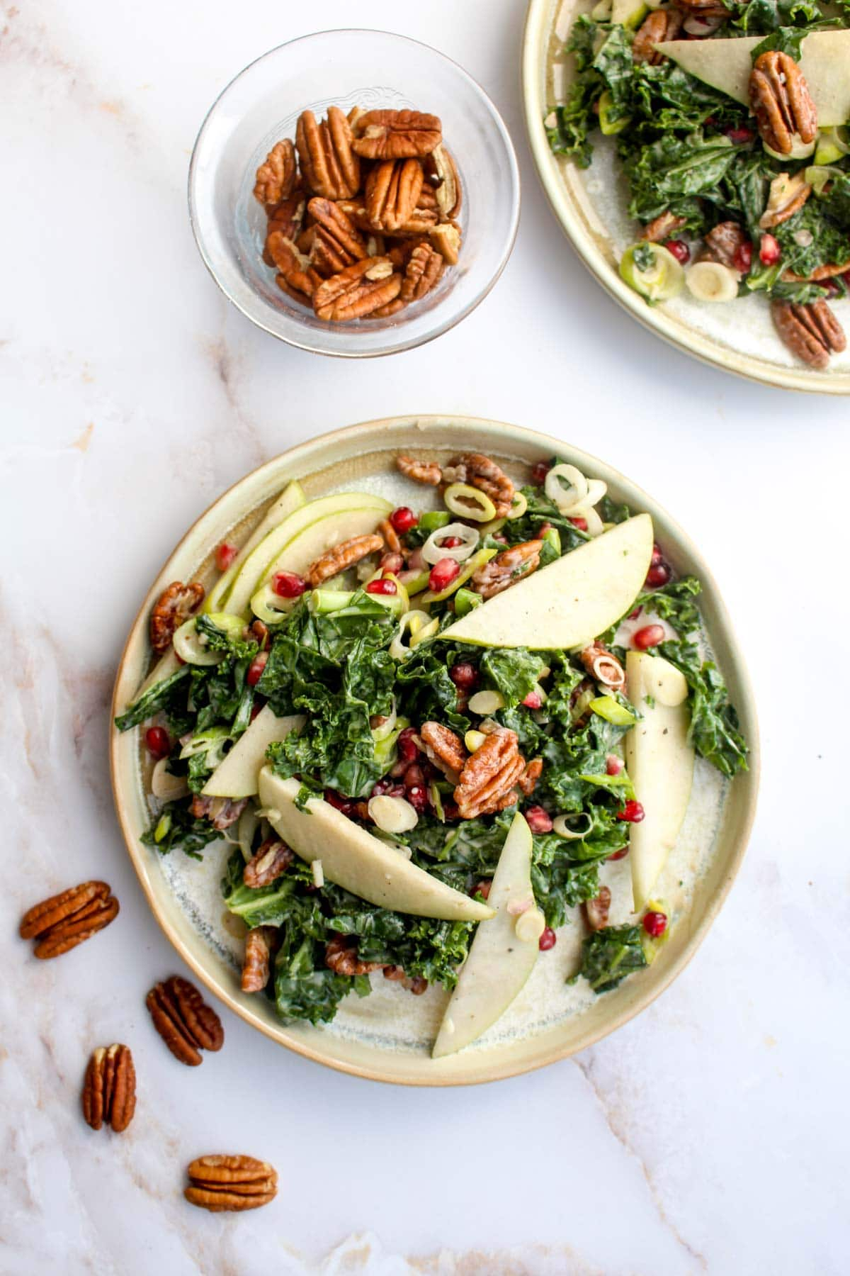 Two plates of winter kale salad with pecans, pears, and pomegranate.
