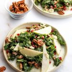 Winter kale salad on a plate with pecans, pomegranate, and pears.