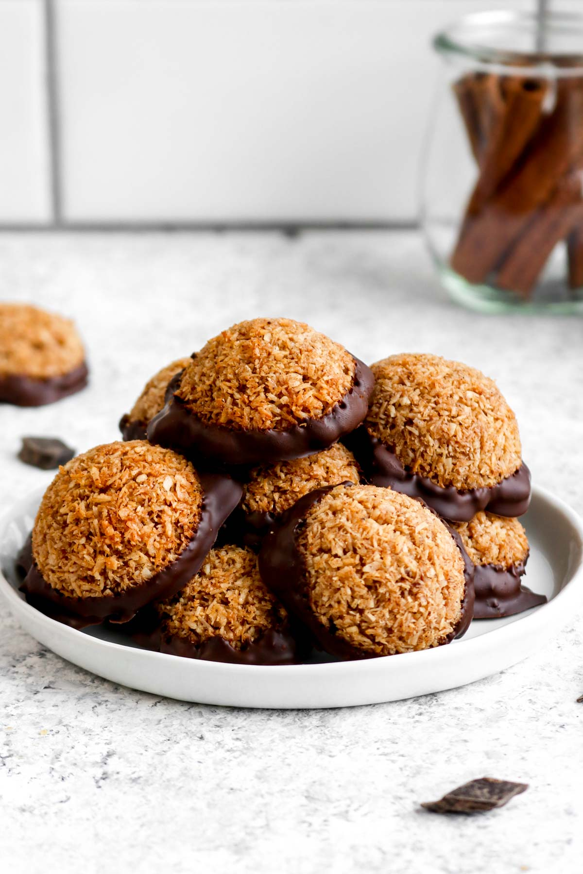 Pumpkin spice macaroon cookies stacked on a plate with chocolate.