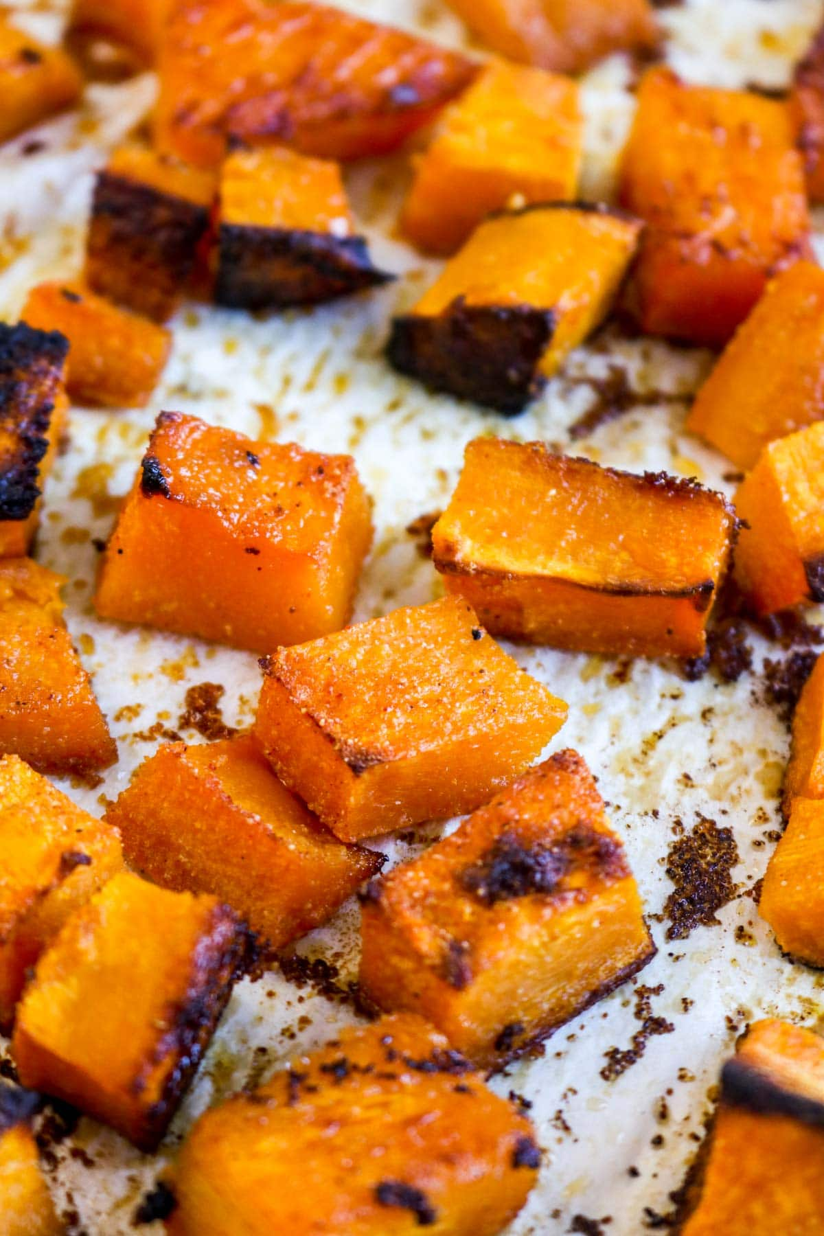 Cubed and roasted butternut squash on a sheet tray.