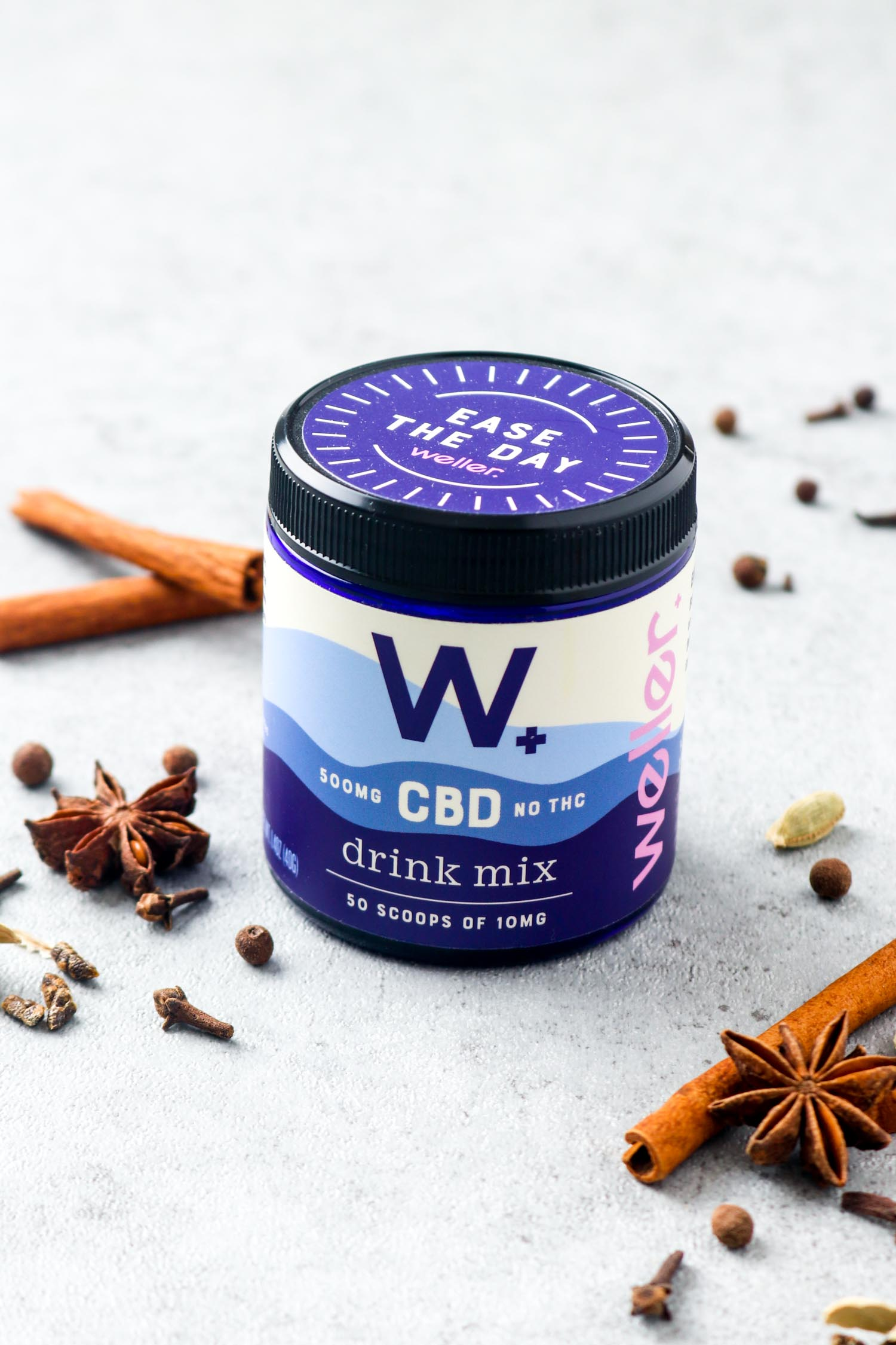 A bottle of Weller CBD drink mix surrounded by chai spices.