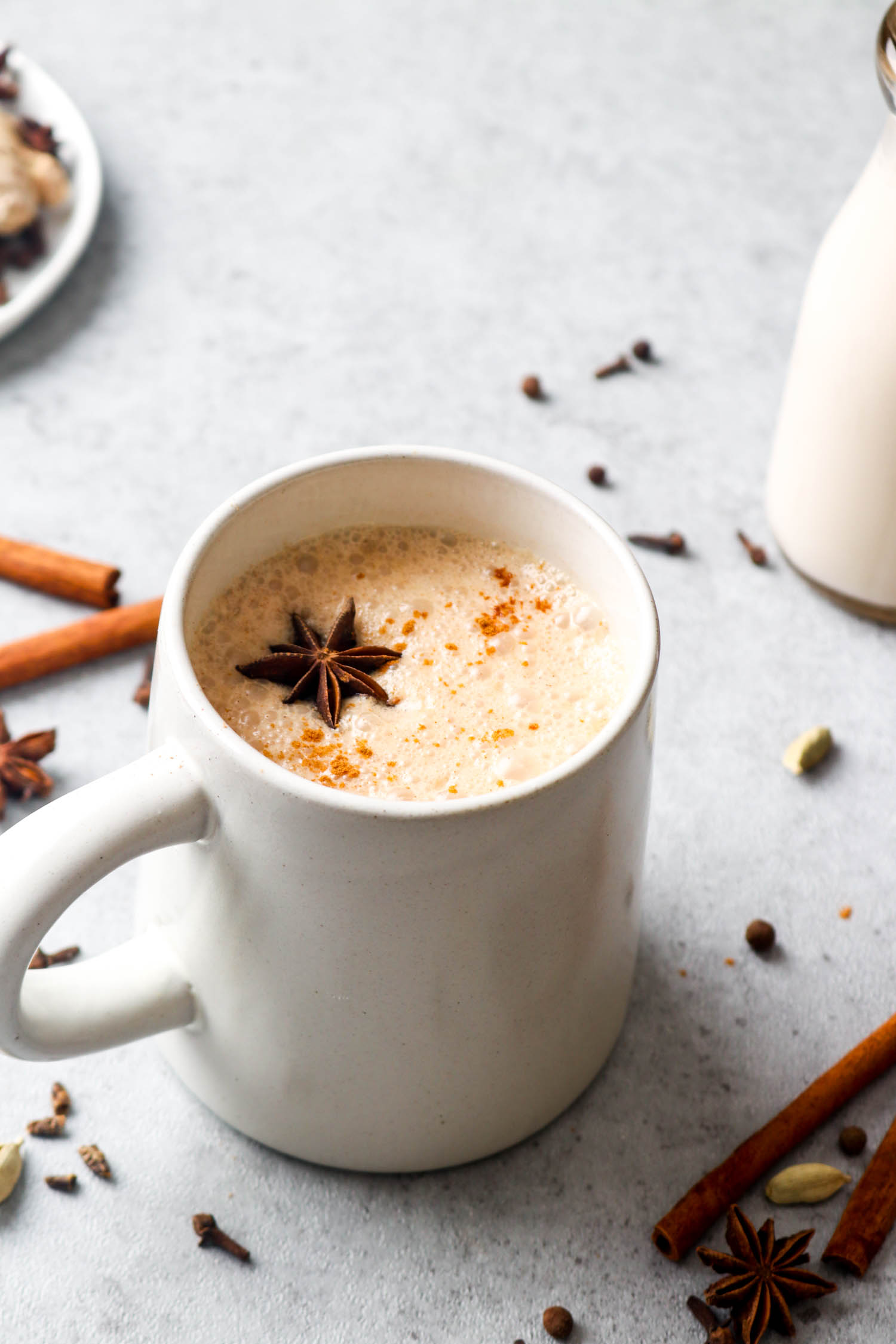 A chill chai latte surrounded by cinnamon sticks, cloves, cardamom, star anise, and coconut milk.