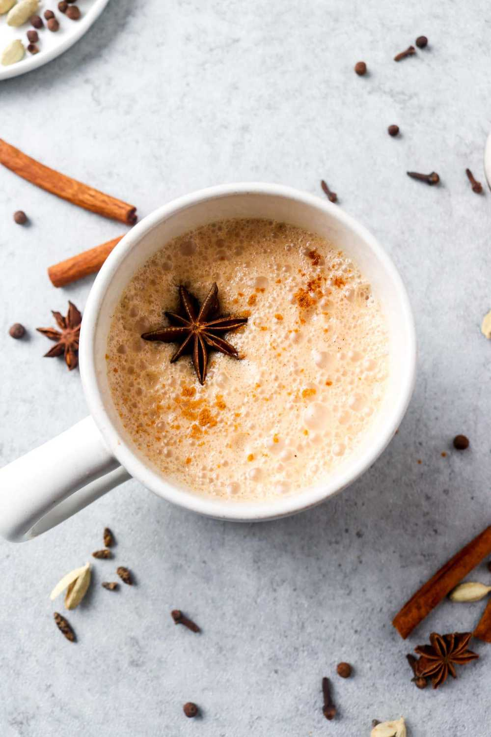 A white mug filled with a chill chai latte surrounded by spices.