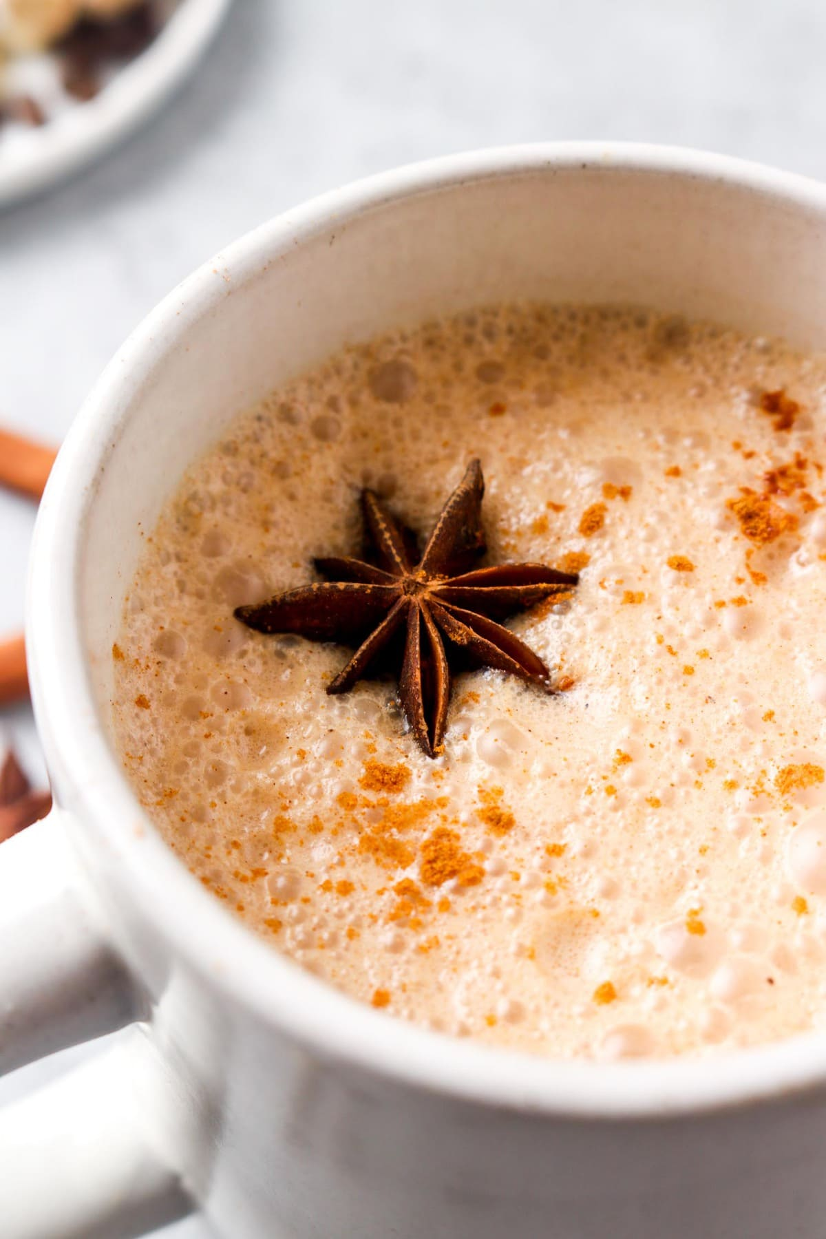 A closeup of a chill chai latte topped with star anise.