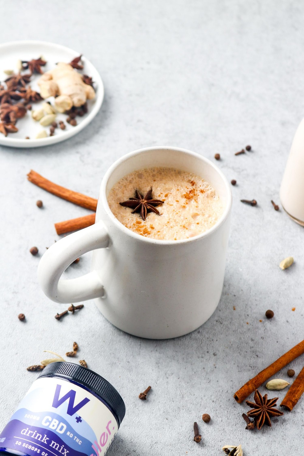 A chill chai tea latte with spiced and a bottle of cbd powder.