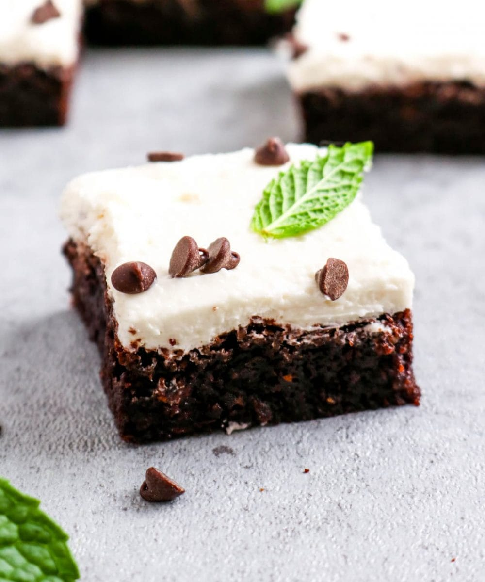 A frosted peppermint brownie with mint leaves and chocolate chips.