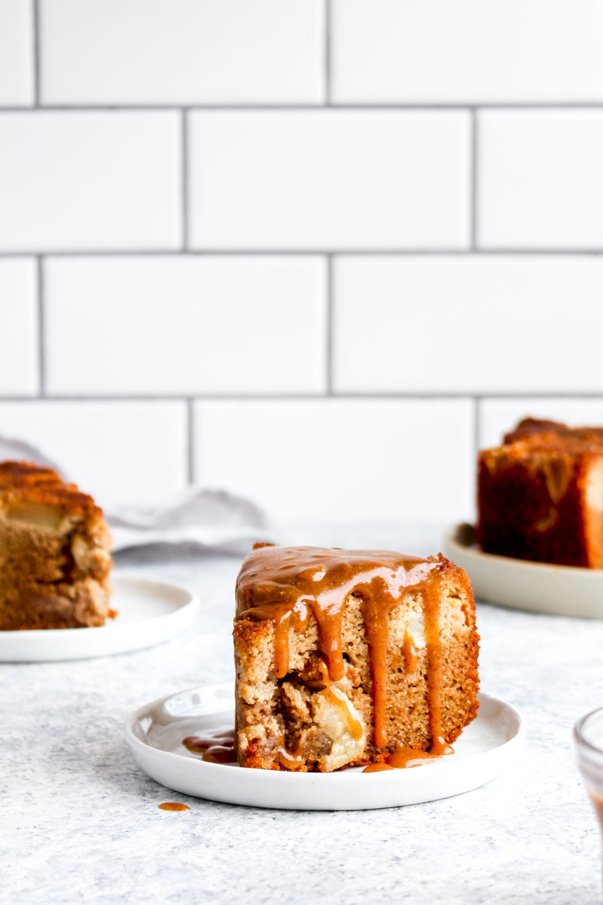 Caramel sauce dripping down the sides of a slice of paleo pear cake.