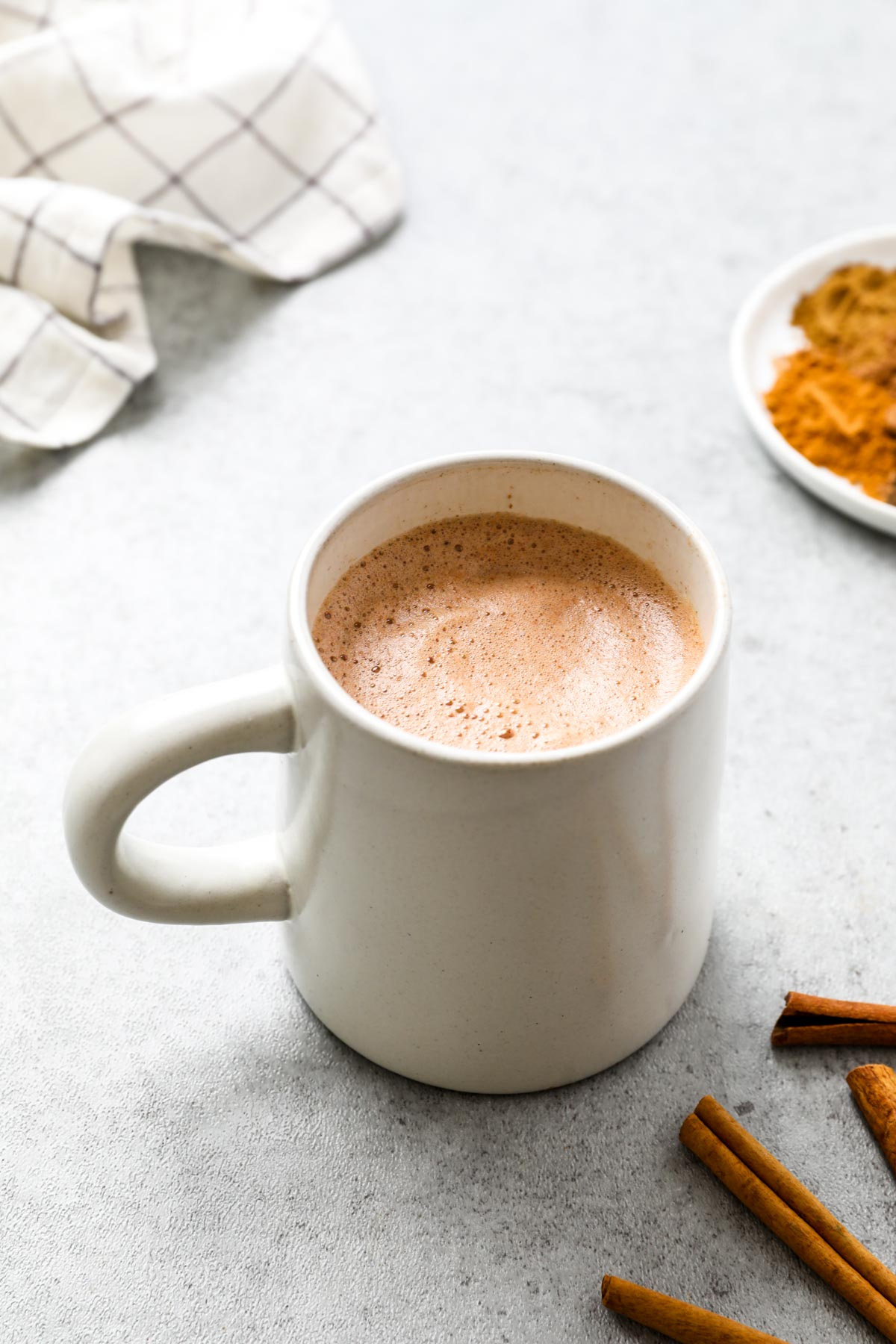 A mug of made healthy vegan hot chocolate mix with soy milk.