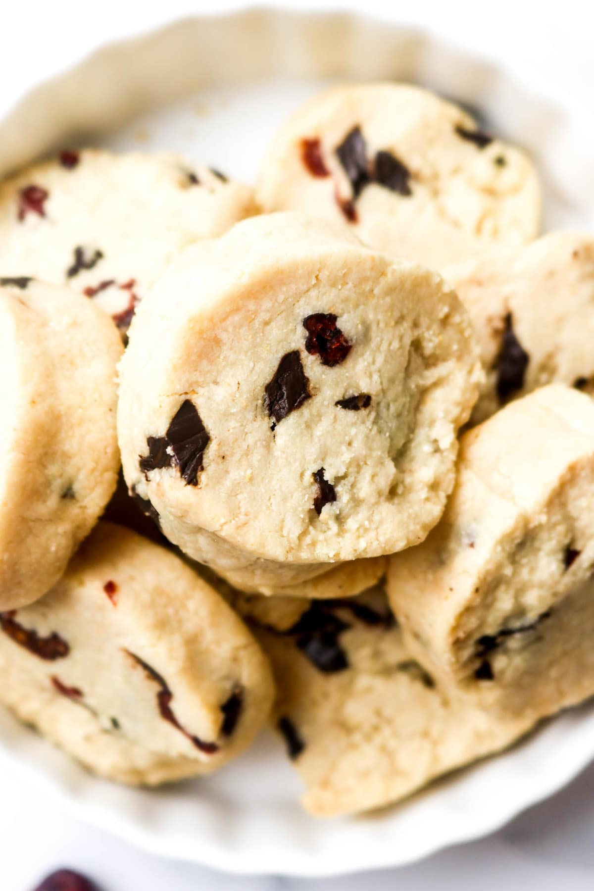 A plate stacked with grain free chocolate chip cranberry shortbread cookies.
