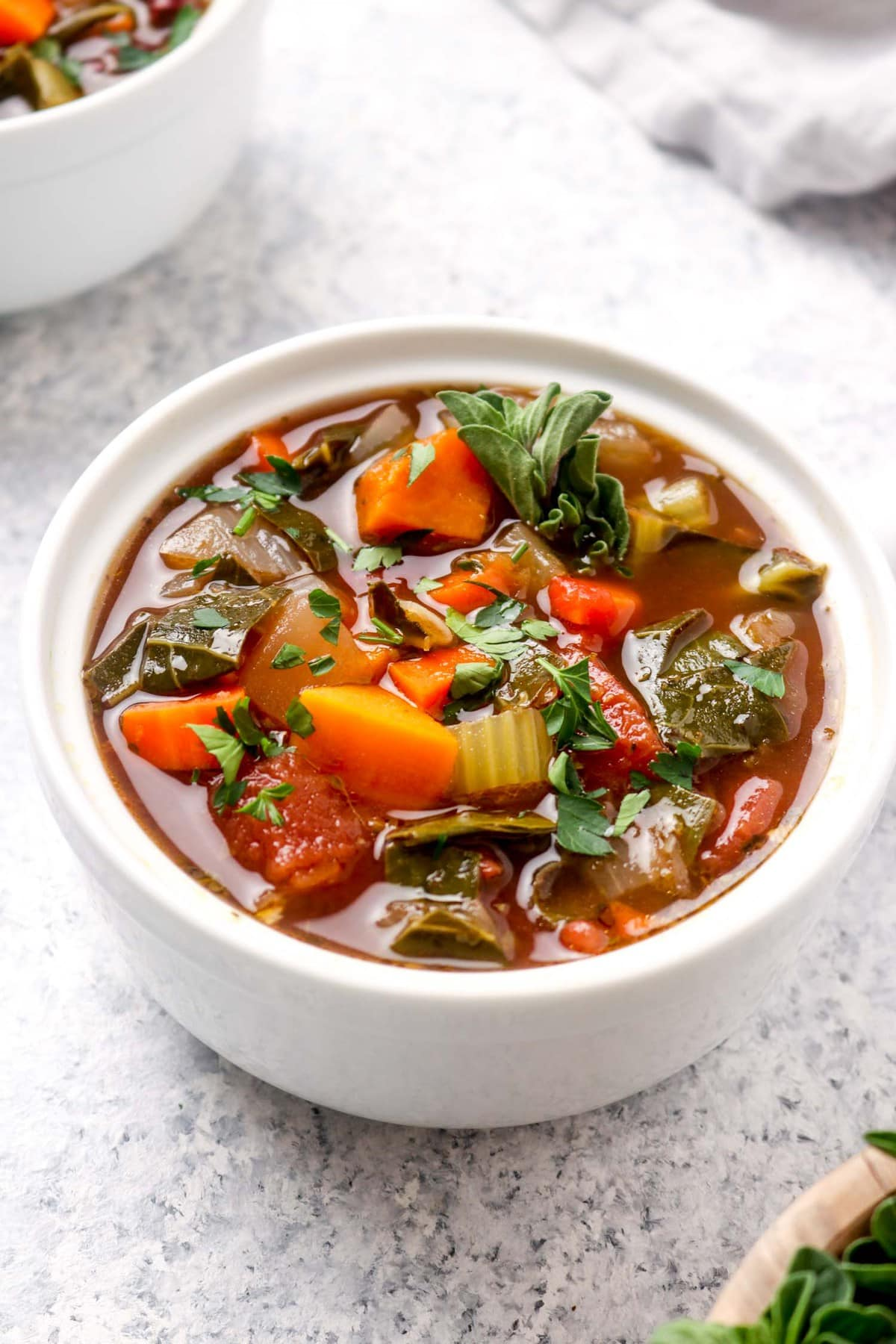 A closeup of Balsamic Vegetable Soup with greens and beans.
