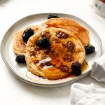 Gluten Free Granola Pancakes on a plate with maple syrup and blackberries.