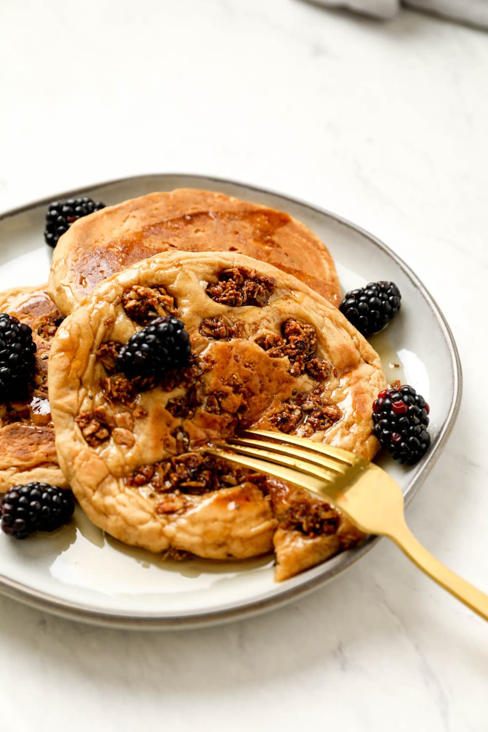 A stack of Gluten Free Granola Pancakes with maple syrup.