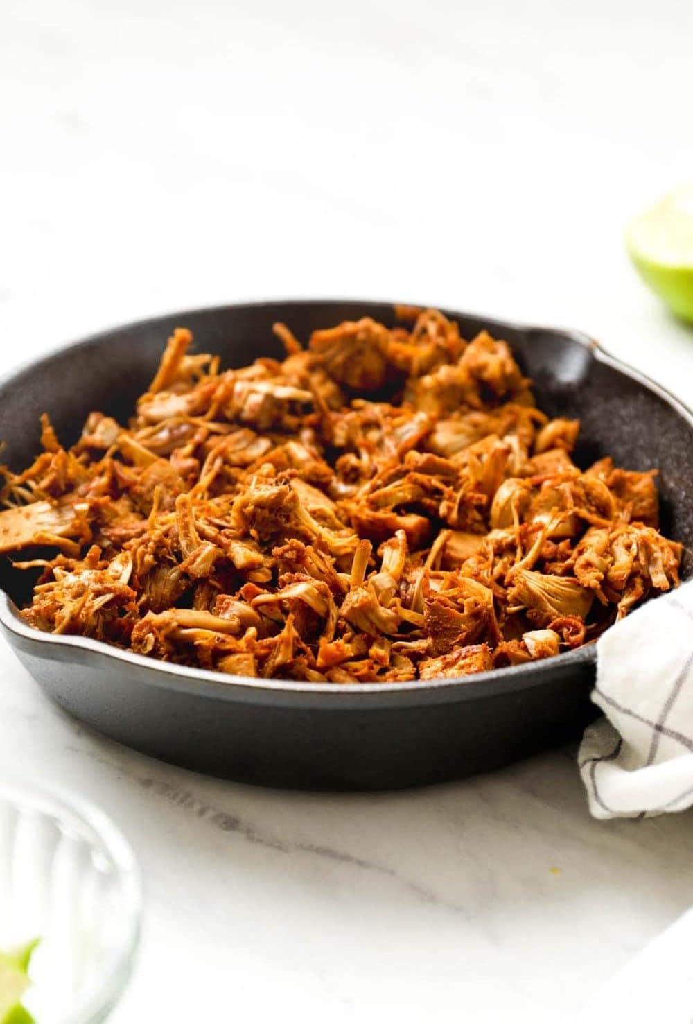 Cooked jackfruit closeup with tortillas and lime.
