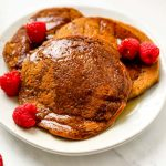 A stack of paleo sweet potato pancakes with maple syrup and raspberries.