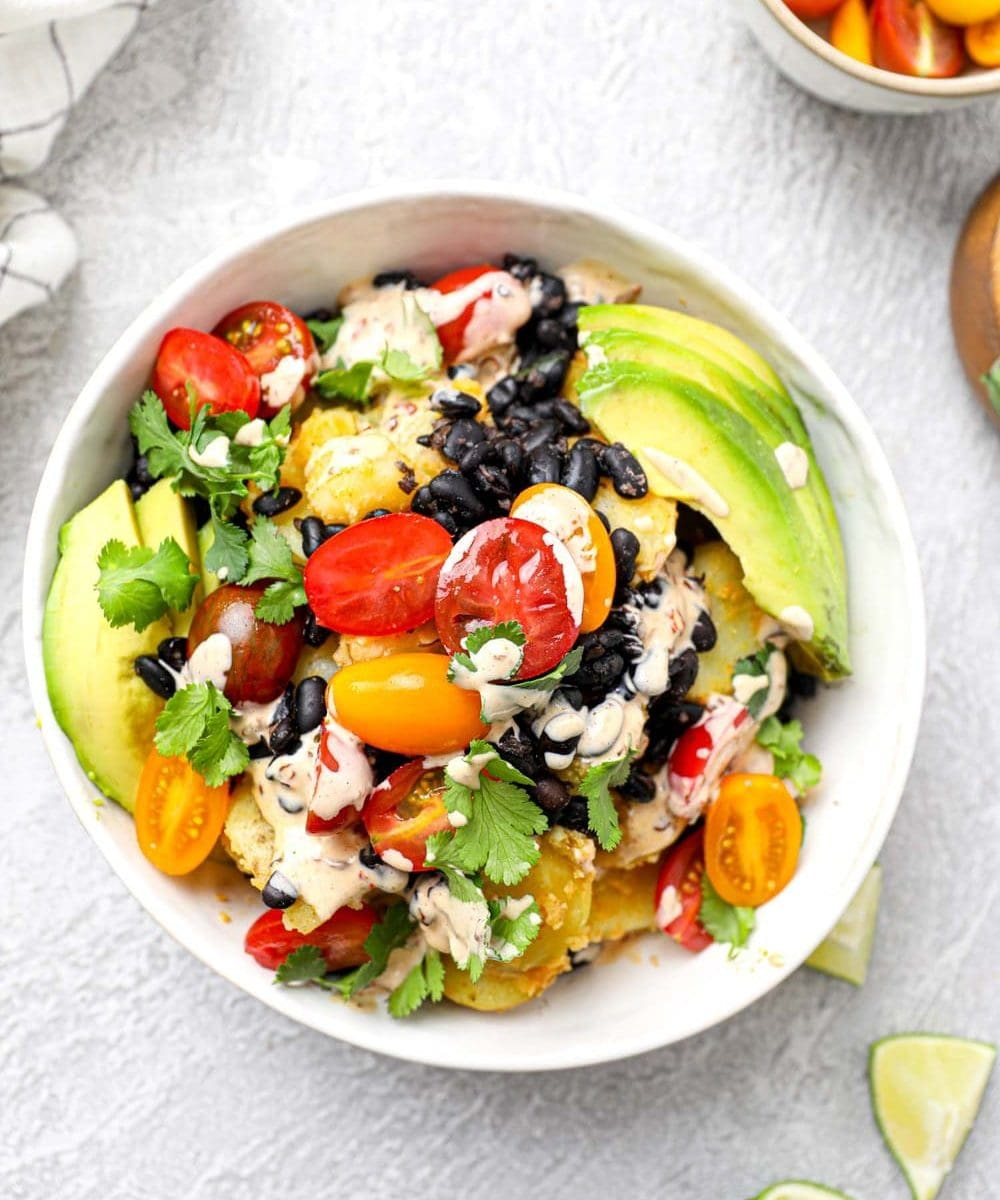 Vegan mexican potato bowl with beans, cilantro, cherry tomatoes, crema, and avocado.