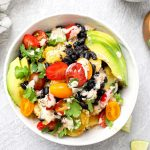 Vegan mexican potato bowl with beans, cilantro, cherry tomatoes, crema, and avocado.