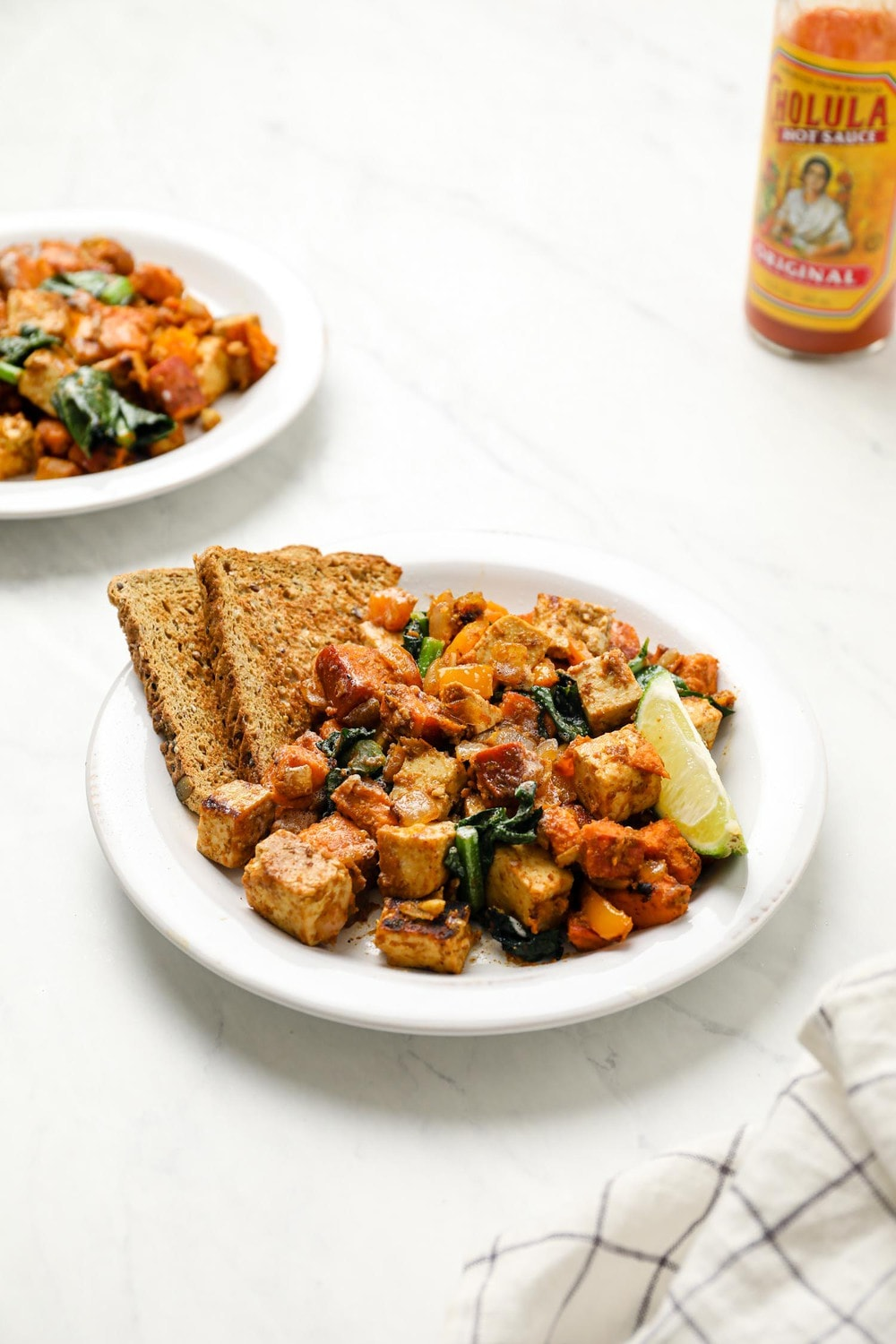 Sweet potato tofu hash with a lime wedge and gluten free toast.