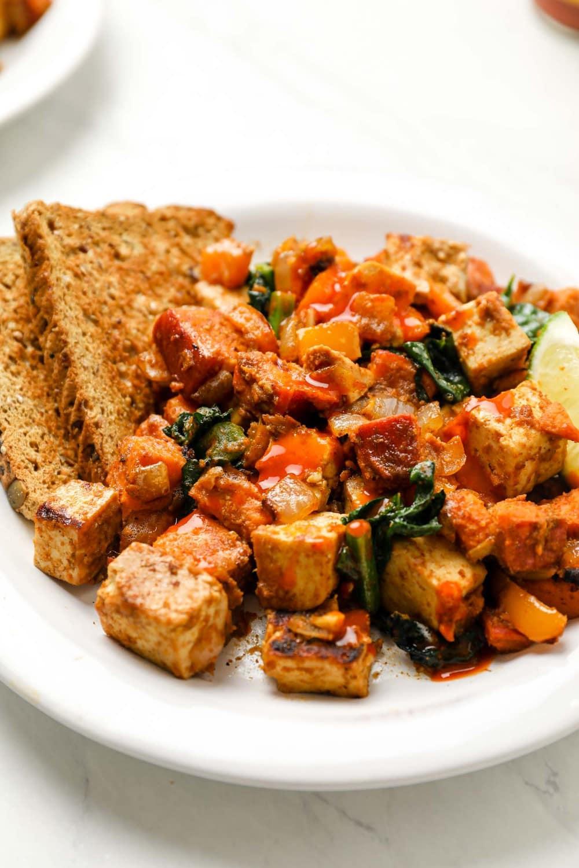 Sweet potato tofu hash with kale and hot sauce.