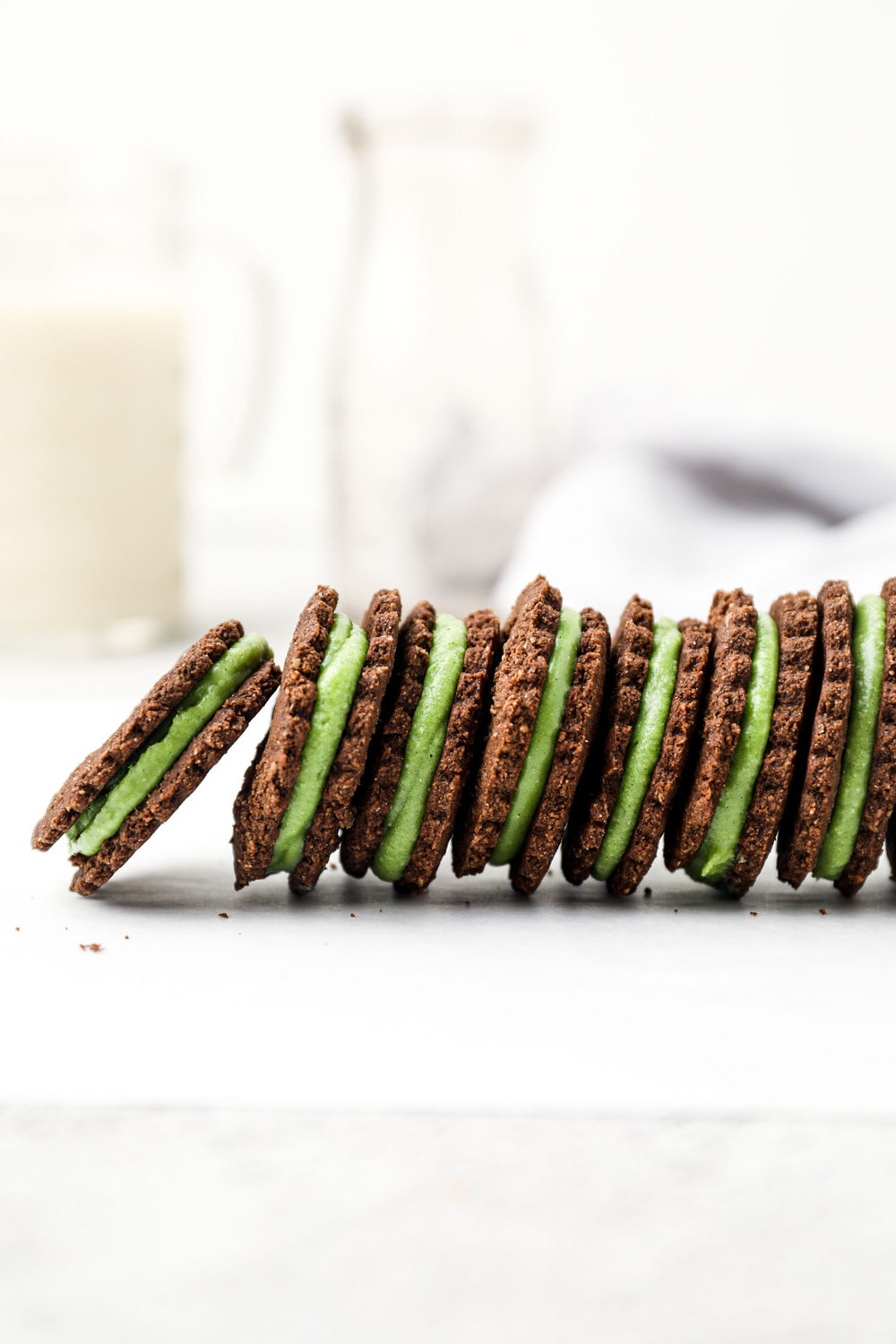 Vegan chocolate sandwich cookies with mint green filling.