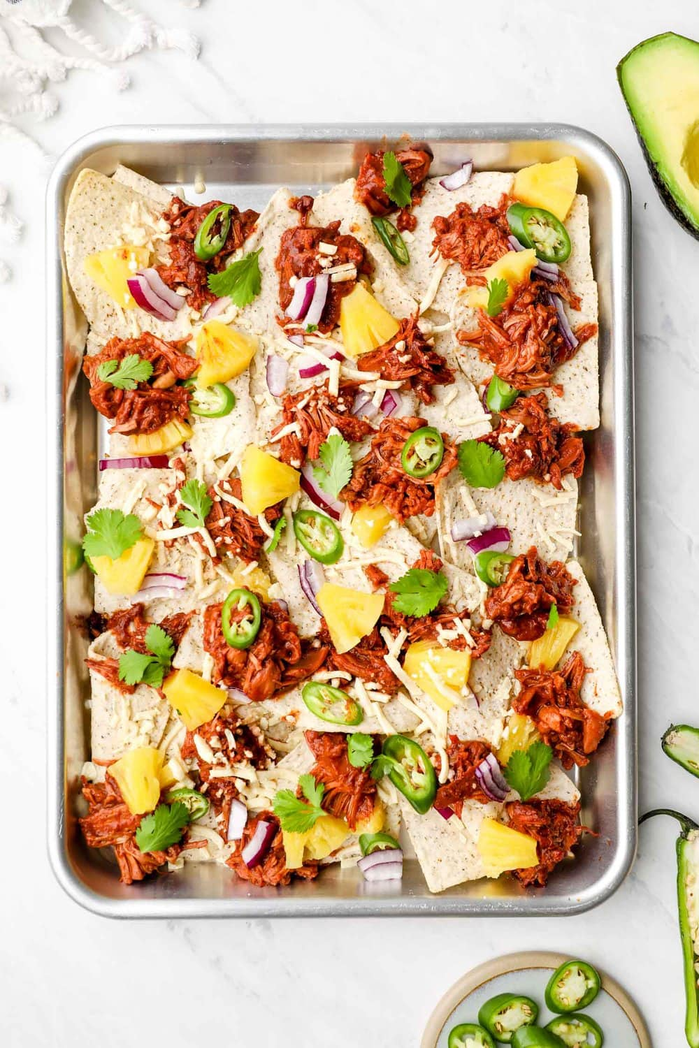 A sheet pan of Barbecue Jackfruit Nachos with pineapple and cheese.