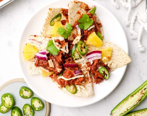 Barbecue Jackfruit Nachos on a plate with tortilla chips, jalapeño slices, cilantro and pineapple.