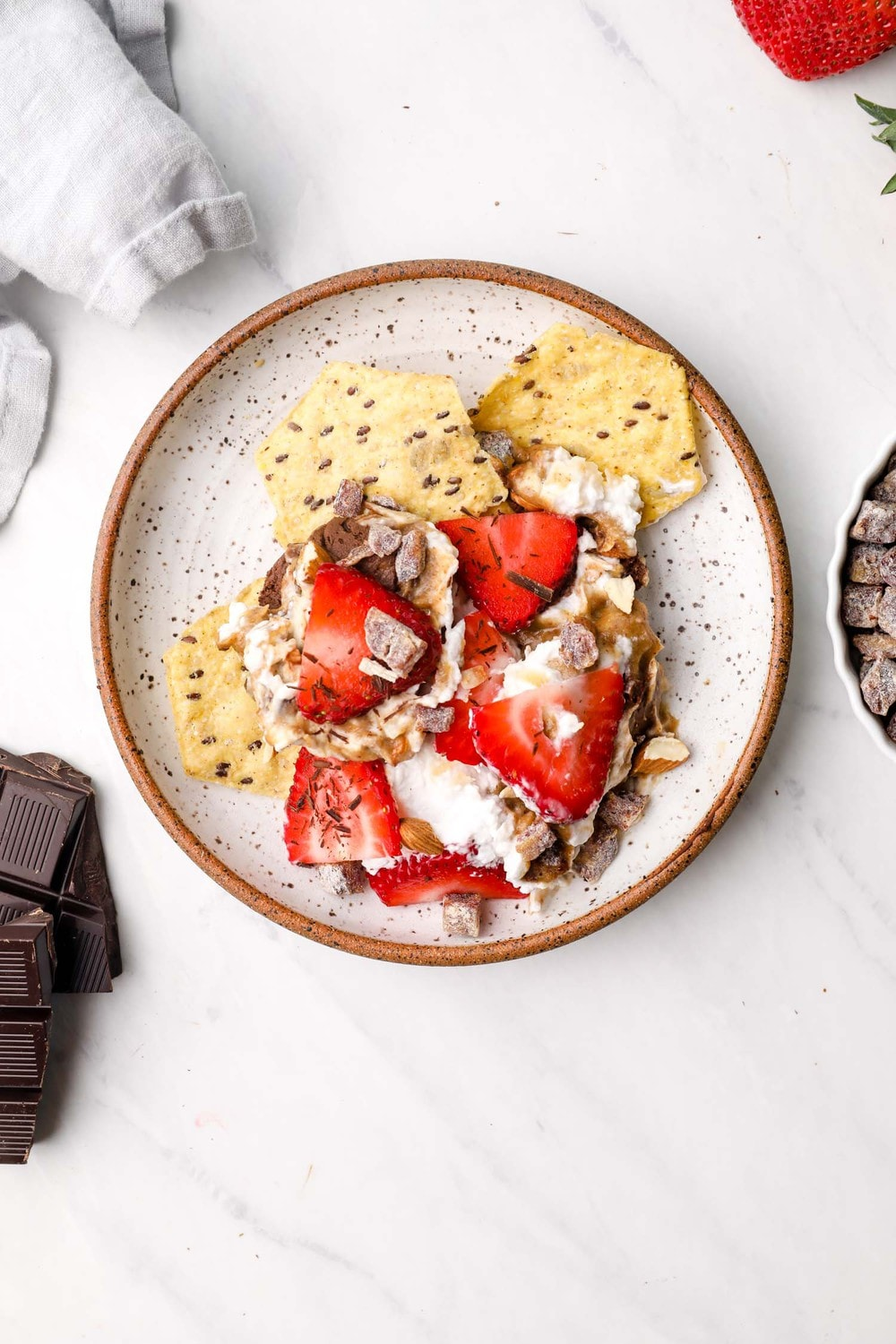 Dessert Seven Layer Dip and crackers on a plate with chocolate and strawberries.