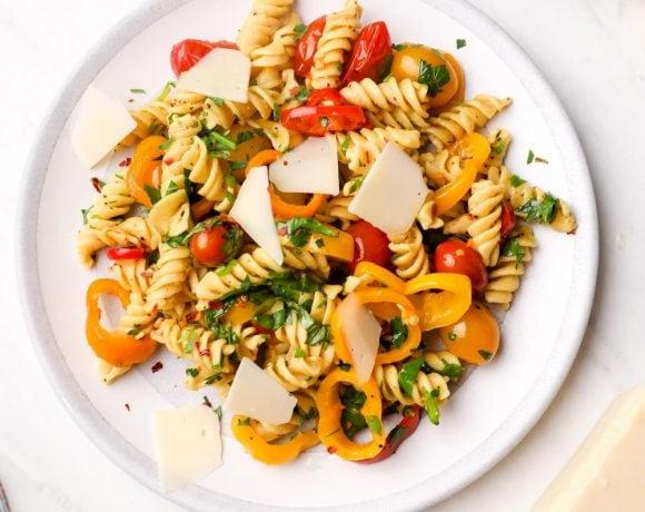 A plate of Vegan Pasta Primavera with parmesan shavings and basil.