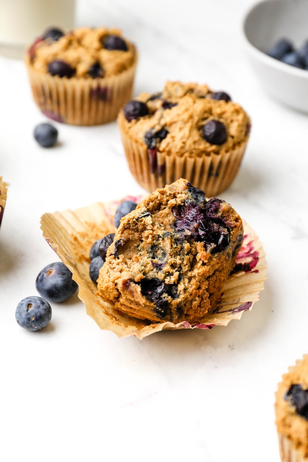 A bite out of a Gluten Free Blueberry Muffins with blueberries.