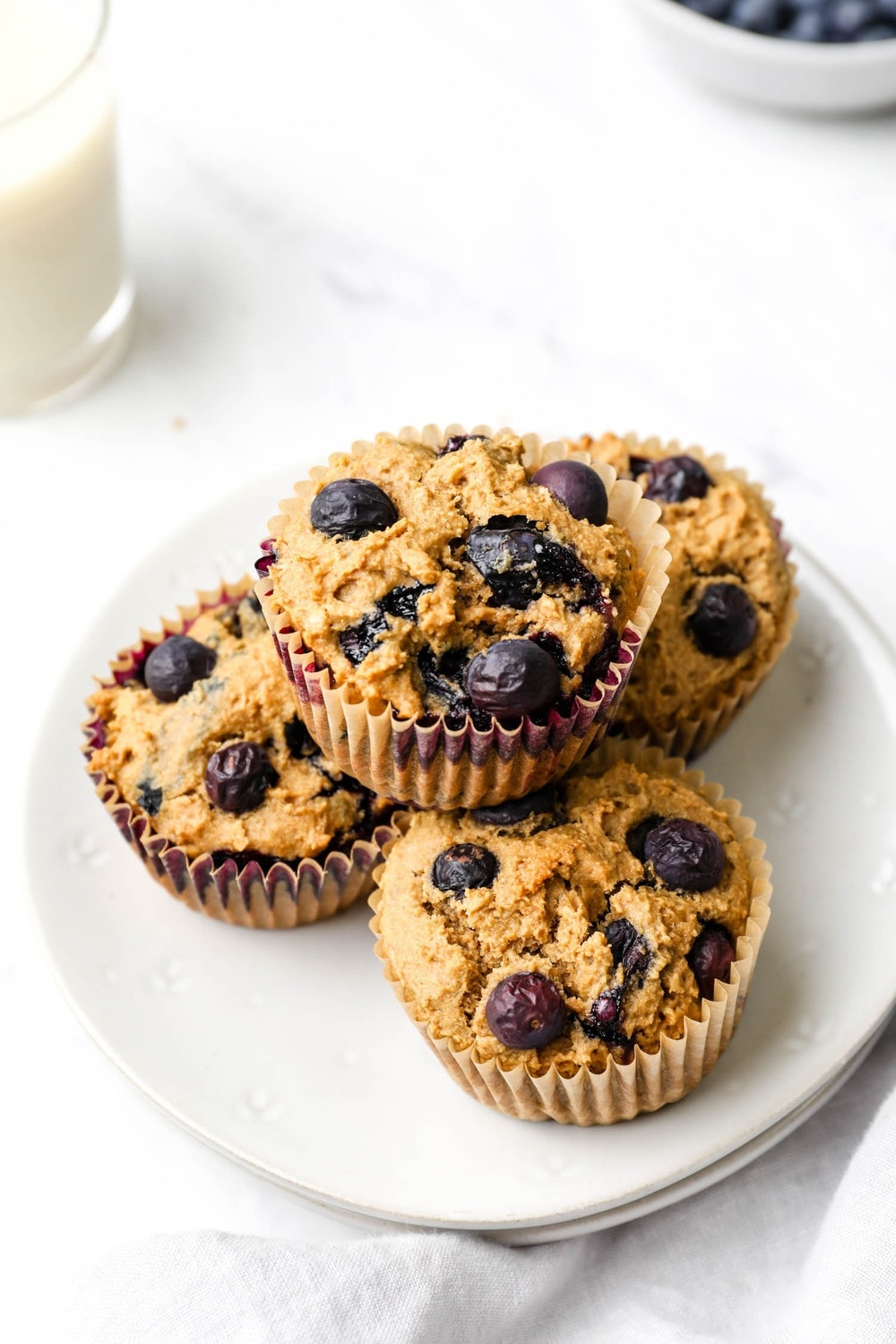 Gluten Free Blueberry Muffins stacked on a serving plate.