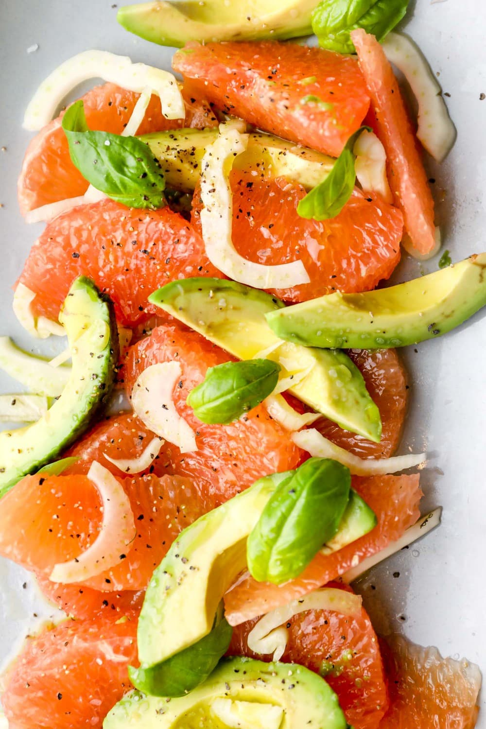 Grapefruit Avocado Salad arranged on a serving plate with a drizzle of olive oil.