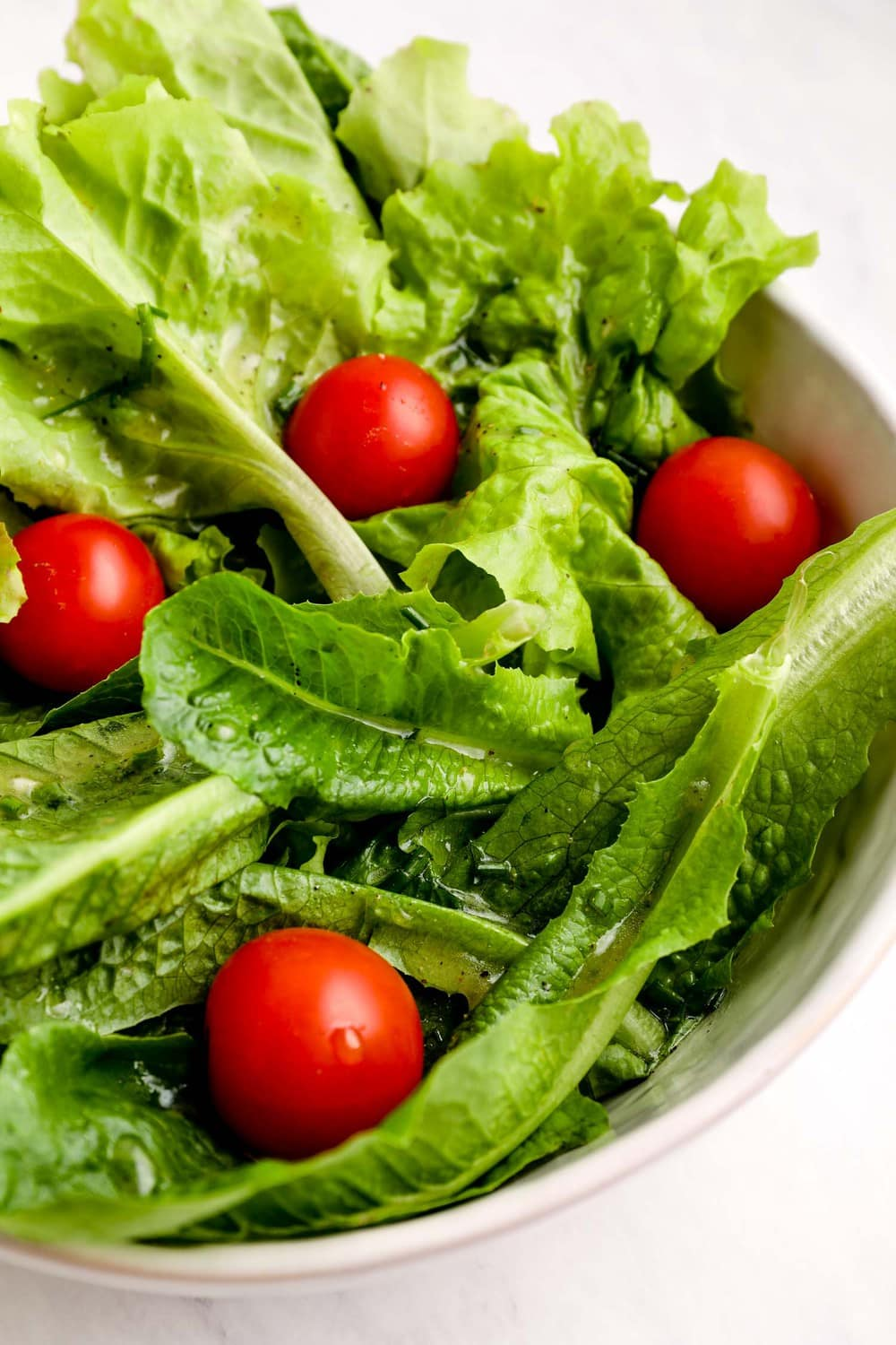 Avocado Oil Salad Dressing on a salad of greens and tomatoes.