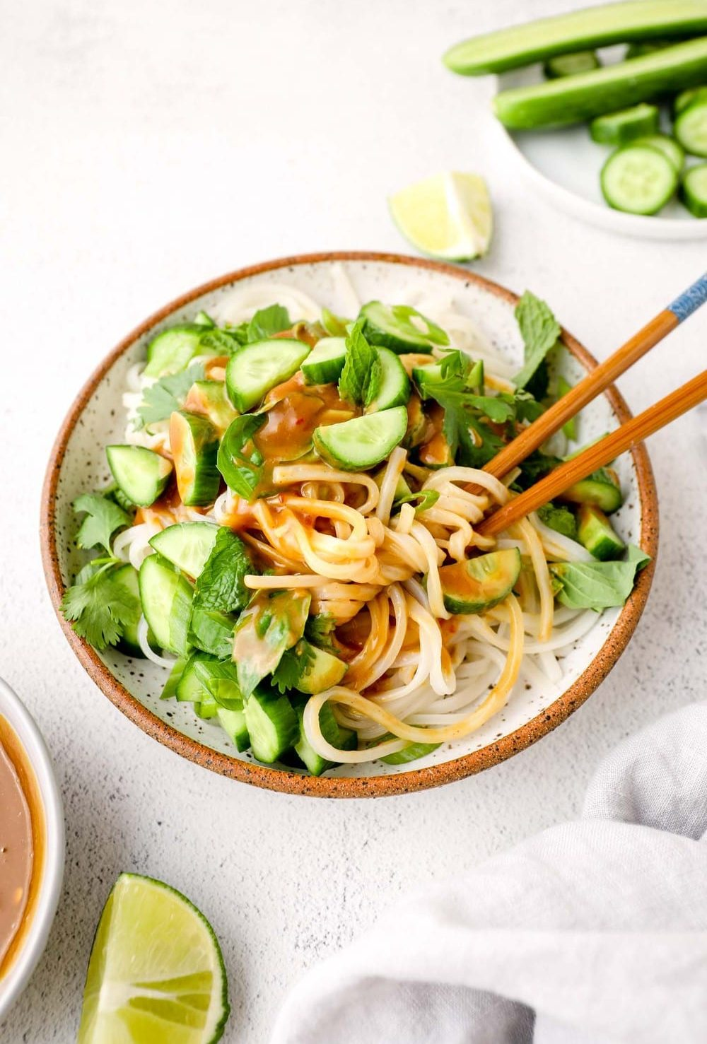 Vegan Summer Roll in a Bowl with chopsticks and peanut sauce.
