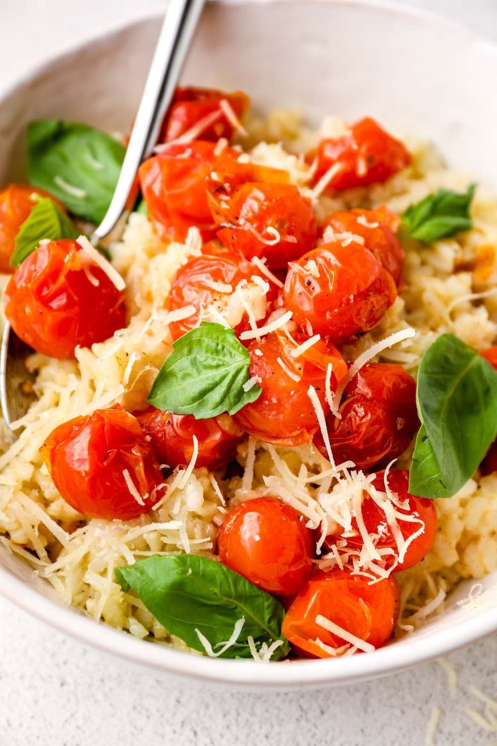 A closeup of roasted tomatoes on vegan risotto.