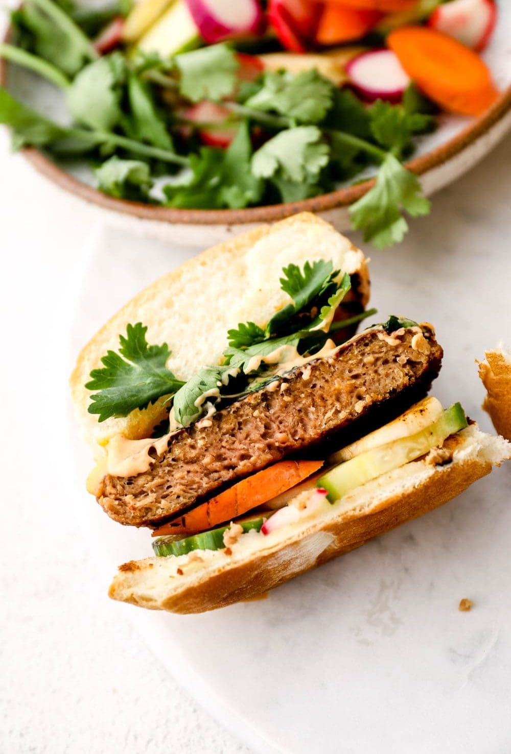 A Bahn Mi Burger cut in half revealing the layers of pickled veggies, burger, sriracha mayo, and cilantro.