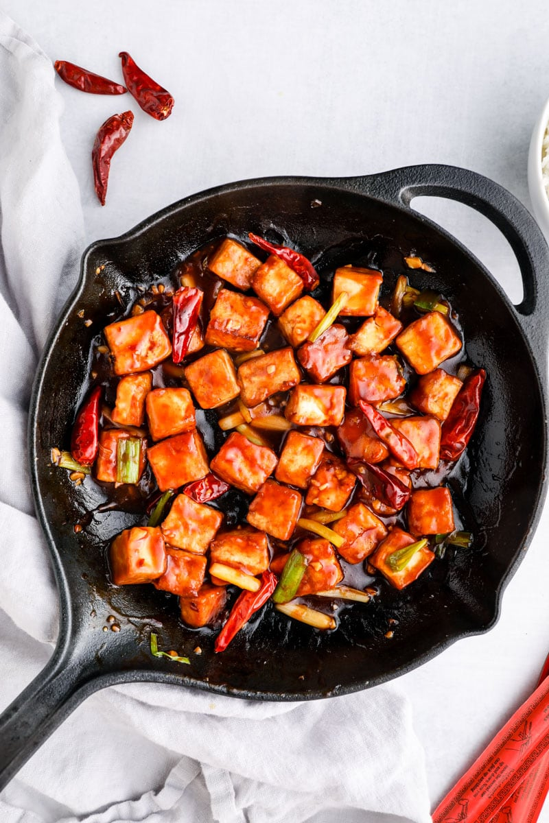 General Tso's Tofu in a skillet with scallions and dried chilis.