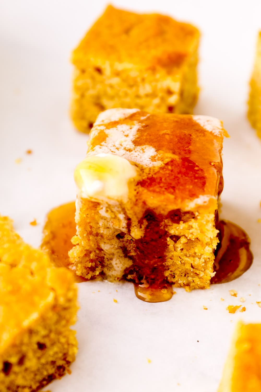 Butter and honey dripping down the sides of a slice of gluten free cornbread.