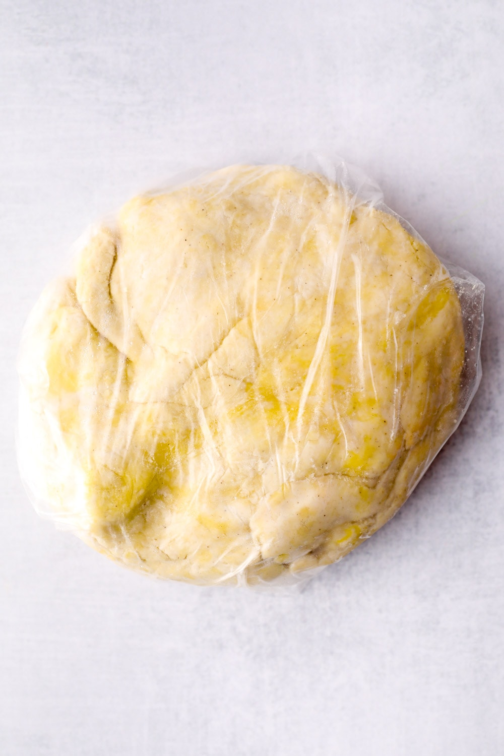 Gluten Free Pie Crust dough wrapped in plastic ready to chill in the fridge for one hour.
