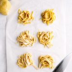 Nests of gluten free pasta on parchment.