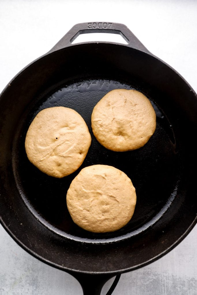 Oat Flour Pancakes in a cast iron skillet, ready to flip.