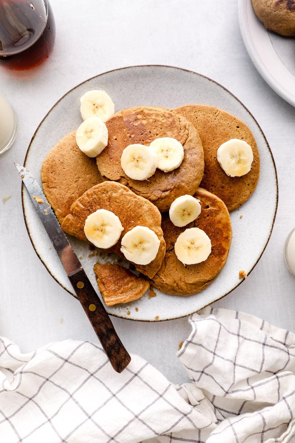 Oat Flour Pancakes on a plate with banana, maple, and cinnamon.